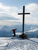 Cross on peak of mountain in snowy mountain scenery _ mountain climber with touring ski has reached the mountain top of the Pichelberg, Italy, Suedtir...