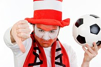 pessimistic Austrian soccer fan with football, making thumb down