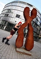 young woman with red hair leaning at a modern art work, Germany, North Rhine_Westphalia, Mediapark, Koeln