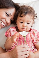 Hispanic mother and daughter looking at flower