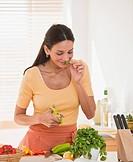 Hispanic woman cutting herbs
