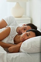 Hispanic couple sleeping in bed