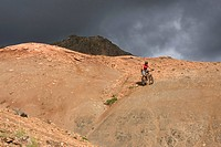 Iceland, Man mountain biking in hilly landscape