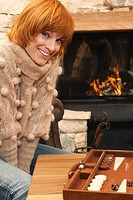 Woman sitting in front of fire place, smiling, backgammon board in foreground