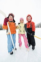 Italy, South Tyrol, Seiseralm, Children 4_5 holding hockey sticks, smiling, portrait