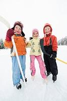 Italy, South Tyrol, Seiseralm, Children 4_5 holding hockey sticks, smiling, portrait