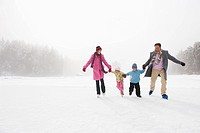 Italy, South Tyrol, Seiseralm, Family holding hands, ice skating