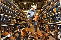 USA, Texas, Dallas, Young man choosing cowboy boots in shoe store