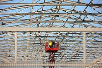 Workers on an aerial work platform (lift platform) during construction of a warehouse in Duisburg, North Rhine-Westphalia, Germany, Europe