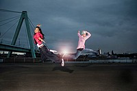 Germany, Cologne, Man and woman jumping, Skyline in background