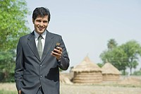 Businessman text messaging on a mobile phone
