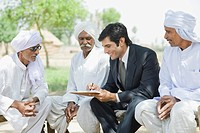 Financial advisor explaining to farmers about agriculture loan