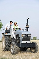 Financial advisor sitting on a tractor with a farmer