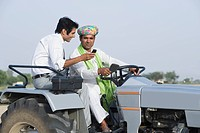 Financial advisor showing a mobile phone to a farmer