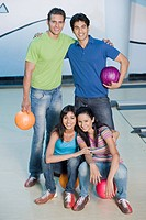 Two young couples with bowling balls in a bowling alley