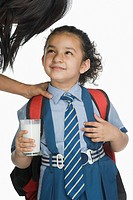 Schoolgirl holding a glass of milk and looking at her mother