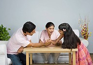 Man arm wrestling with his daughter and his wife watching