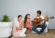 Man sitting with his family and playing a guitar