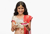 Portrait of a girl smiling and holding a traditional Diwali thali