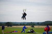 Two people in tandem parachute preparing for landing