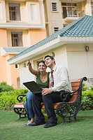 Couple sitting on the bench with laptop and pointing