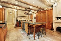 Country kitchen in luxury home with wood ceiling beams