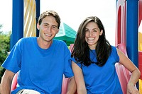 Two teens together on a slide smiling