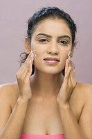 Portrait of a young woman applying moisturizer on her face