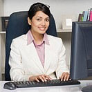 Portrait of a businesswoman working on a desktop PC in an office
