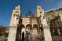 Clergyman in front of the cathedral (Norman architecture) in Cefalu, Sicily, Italy
