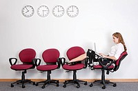 Businesswoman sitting with legs on chairs and using laptop (thumbnail)