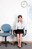 Businesswoman sitting on chair with laptop and holding mobile phone