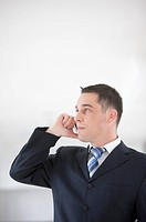 Businessman using mobile phone and looking away
