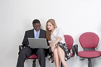 Business people sitting on chair and looking at the laptop together
