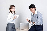 Business people holding coffee cups and smiling at the camera