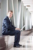 Businessman sitting with laptop and smiling at the camera