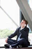 Businessman sitting, using mobile phone and looking up