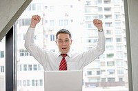 Businessman raising fists with confidence and looking at the camera