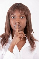 Close-up of young woman putting finger on lips and looking at the camera (thumbnail)