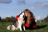 Siberian Husky Canis lupus f. familiaris, woman with her dog on a meadow, Germany