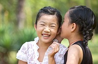 Two girls whispering and smiling happily
