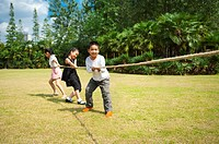 Children standing in a row and playing tug_of_war together