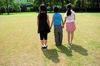 Three children holding hands together and standing in a row
