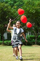 Children holding balloon and running on the lawn together