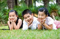 Three children lying on grass with hands on chins, looking at the camera together