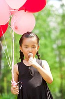 Girl holding balloon and eating ice cream