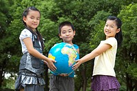 Three children holding the globe together and looking at the camera