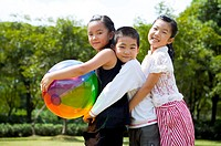 Three children embracing together with a ball and looking at the camera