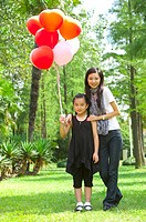 Young woman and girl standing on the lawn together and holding balloon