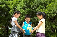 Three children holding the globe together and looking down, Child